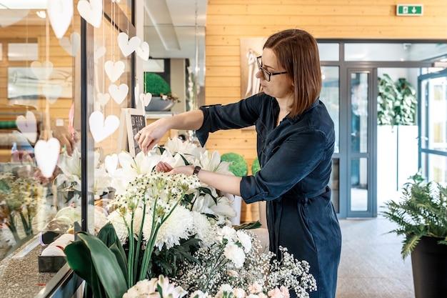 Florista jovem cuida das flores em sua loja. conceito de empresa de pequeno porte, loja de flores. trabalho favorito. vista lateral.