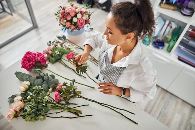 Florista jovem elegante olhando flores diferentes