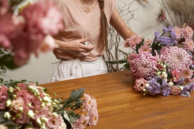 Florista jovem em seu estúdio fazendo um lindo buquê