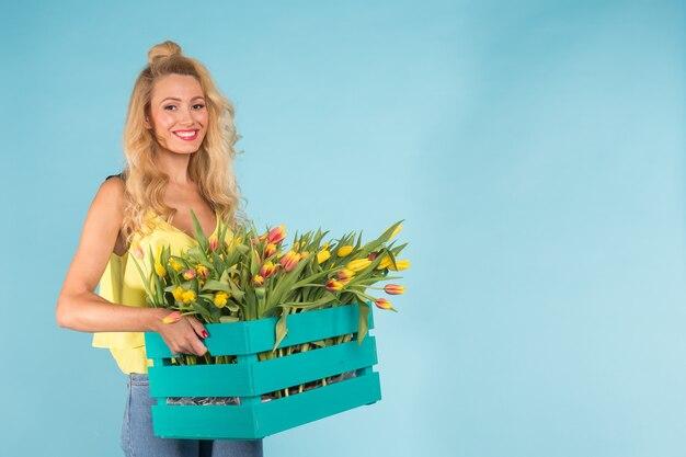 Florista loira caucasiana feliz rindo e segurando uma grande caixa de tulipas na parede azul com espaço de cópia