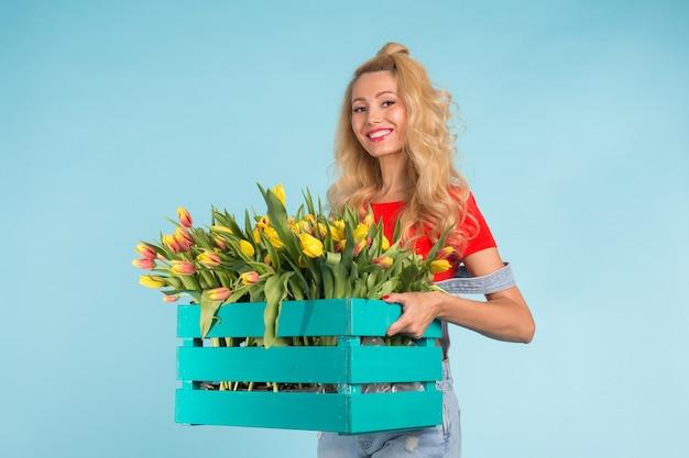 Florista loira caucasiana feliz rindo e segurando uma grande caixa de tulipas na parede azul
