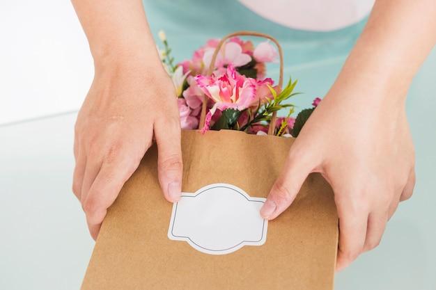 Florista mão segurando o saco de papel cheio de flores