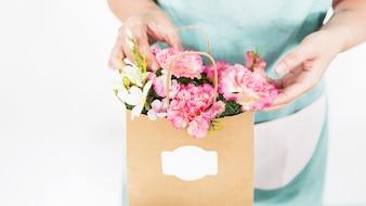 Florista mão tocar flores em saco de papel