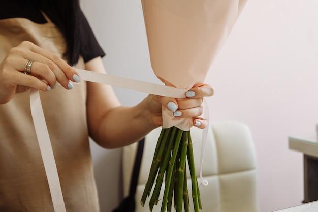 Florista menina usando uma tesoura decora um buquê de tulipas flores em uma loja de flores