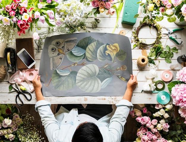 Florista, mostrando o papel de espaço vazio design na mesa de madeira com flores frescas decorar