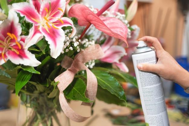 Florista na loja de flores usando spray. florista em floricultura com lata de spray, polimento de folhas.