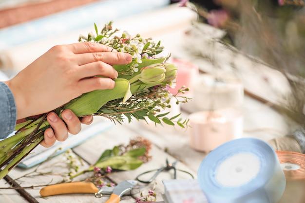 Florista no trabalho: as mãos femininas de mulher fazendo moda moderno buquê de flores diferentes