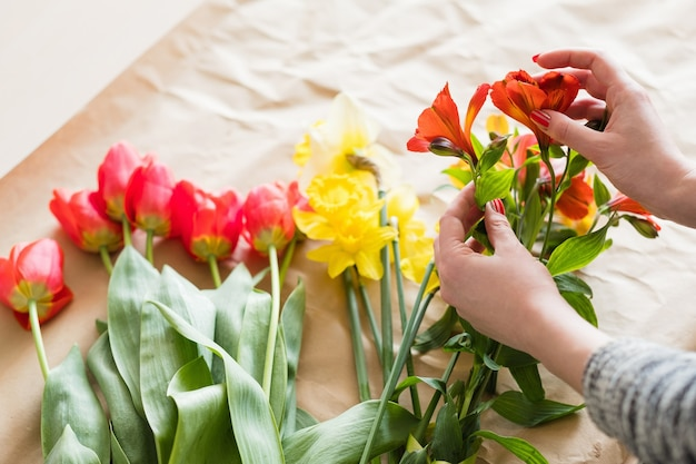 Florista no trabalho. mãos de mulher organizando um buquê de flores de primavera de uma variedade de tulipas vermelhas de alstroemeria e narciso