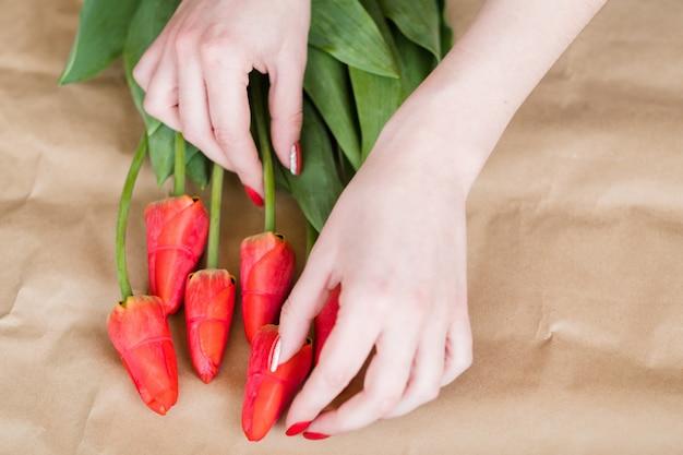 Florista no trabalho. mulher com as mãos organizando um buquê de flores de primavera de tulipas vermelhas.