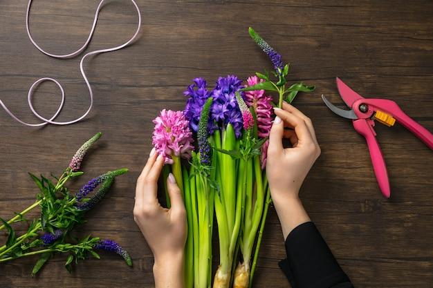 Florista no trabalho, mulher fazendo moda buquê moderno de flores diferentes em fundo de madeira