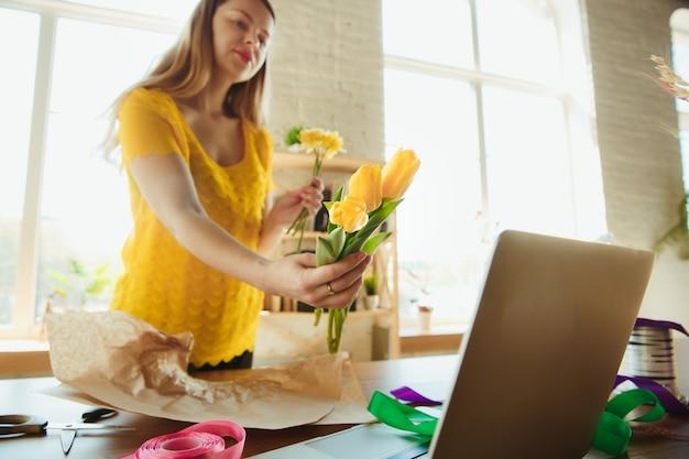 Florista no trabalho: mulher mostra como fazer buquê com tulipas. jovem mulher caucasiana dá workshop online de fazer um presente, um presente para a celebração. trabalhar em casa enquanto conceito isolado, em quarentena.