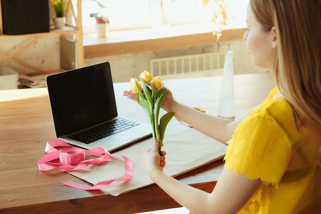 Florista no trabalho: mulher mostra como fazer buquê com tulipas.