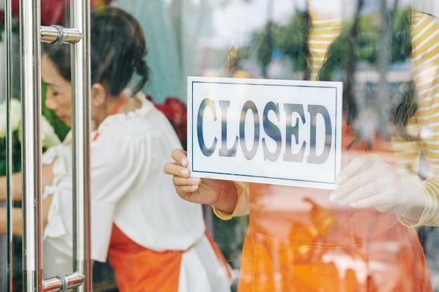 Florista pendurando placa na porta da loja e fechando loja devido às restrições da pandemia de coronavírus