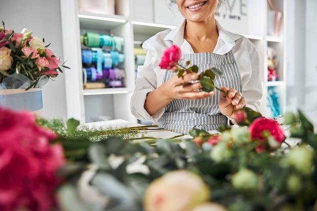 Florista posando com rosas no local de trabalho