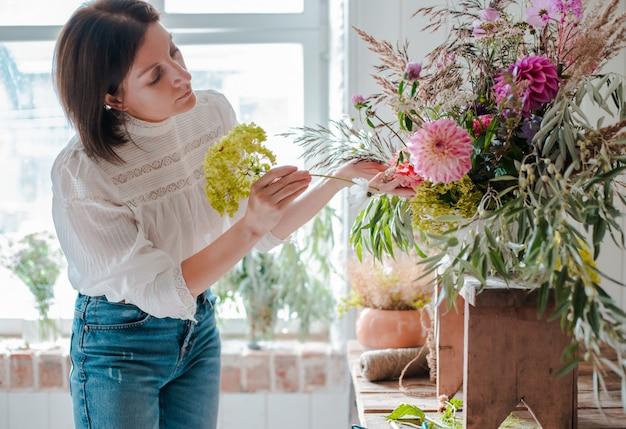 Florista profissional feminina prepara o arranjo de flores silvestres.