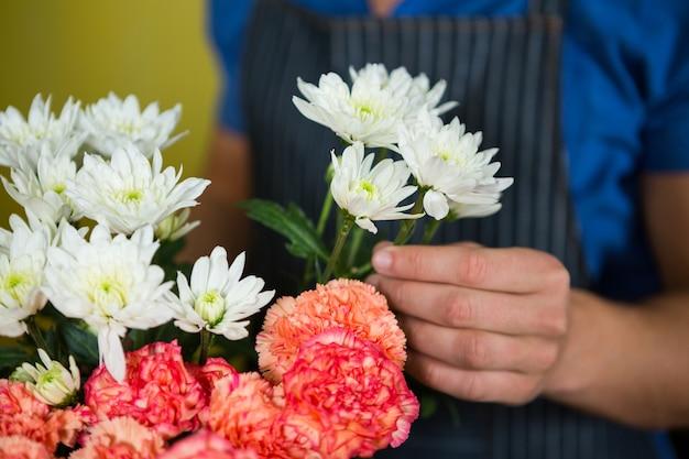 Florista segurando flores em loja de flores