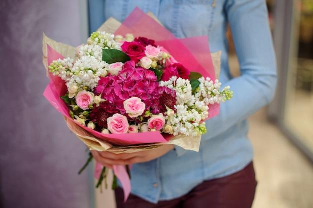Florista segurando um lindo buquê branco e rosa de flores