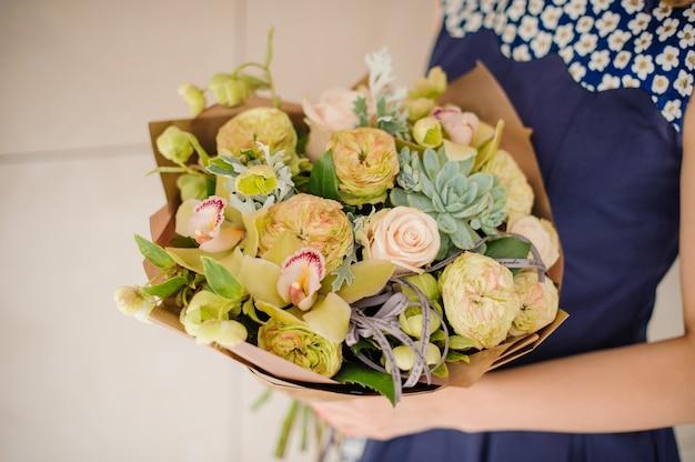 Florista segurando um pequeno buquê verde de flores nas mãos