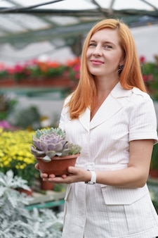 Florista sorridente e feliz em seu berçário, segurando um vaso de combinação de suculentas nas mãos enquanto cuida das plantas de jardim na estufa