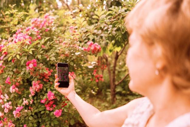 Florista tira uma foto de flores com seu telefone no jardim