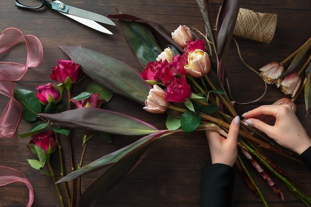 Florista trabalhando, mulher fazendo buquê moderno de flores diferentes na superfície de madeira