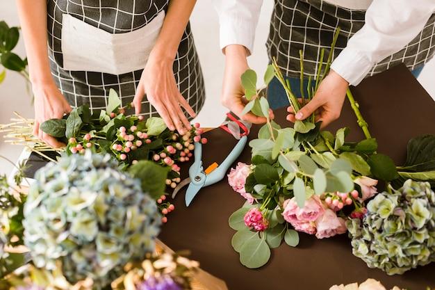 Floristas de close-up fazendo buquê com rosas rosa