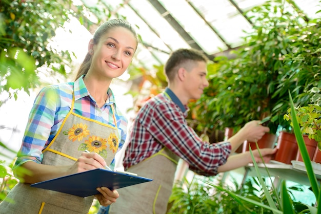 Floristas de sorriso novos homem e funcionamento da mulher.