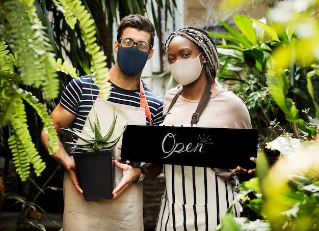 Floristas em máscara facial com sinal aberto durante novo normal