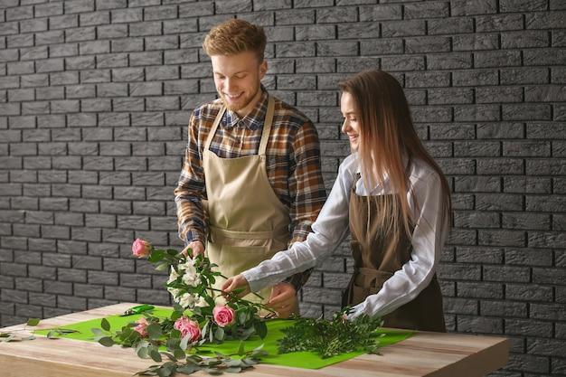 Floristas fazendo buquê na mesa contra a superfície escura