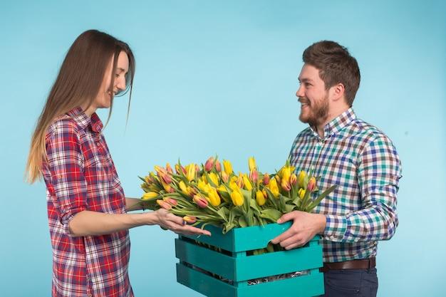 Floristas felizes consertando tulipas em uma grande caixa de madeira sobre fundo azul