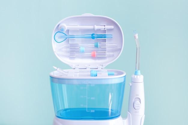 Flosser de água, irrigador oral dental em um fundo azul. cuidados com equipamentos odontológicos. irrigador para boca