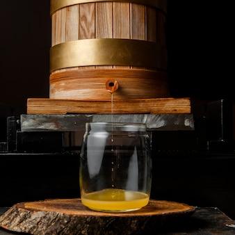 Fluindo óleo na vista lateral do frasco de vidro na peça escura e de madeira