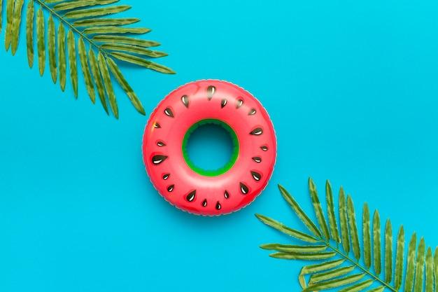 Flutuador de piscina de melancia e folhas de palmeiras de verão