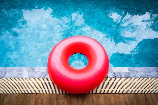 Flutuador vermelho da associação, anel que flutua em uma piscina azul de refrescamento com sombra da árvore de coco.