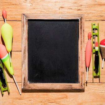 Flutuadores de pesca com ardósia em branco na placa de madeira