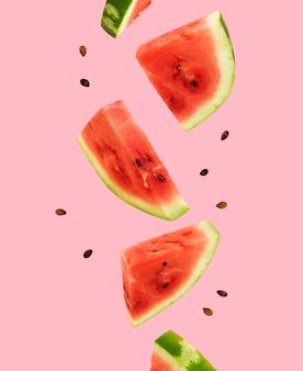 Flutuando, voando, levitando melancia fatiada em fundo rosa. frutas de verão, frutas vermelhas. comida criativa minimalista e moderna. conceito de melancia dia 3 de agosto.