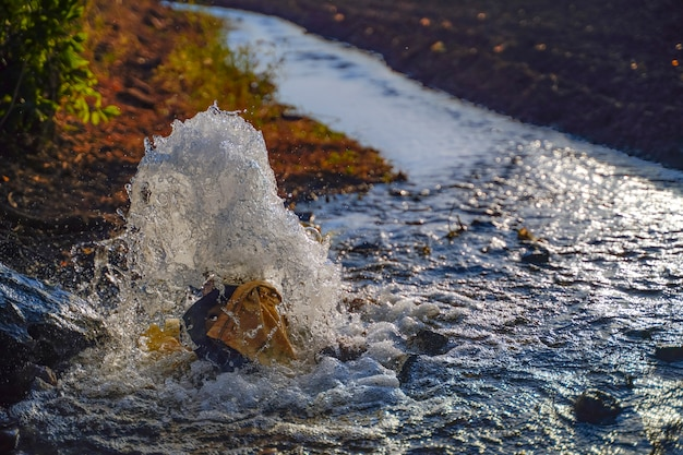 Fluxo de água de irrigação do tubo ao canal para campos agrícolas, flash de água em câmera lenta