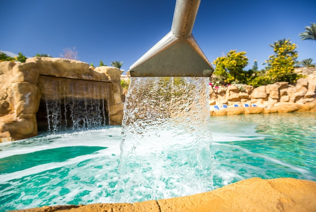 Fluxo de água de uma cachoeira artificial na piscina externa