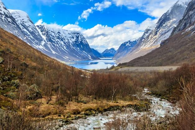 Fluxo de água para baixo do rio para o lago com fundo de montanha de boné de neve