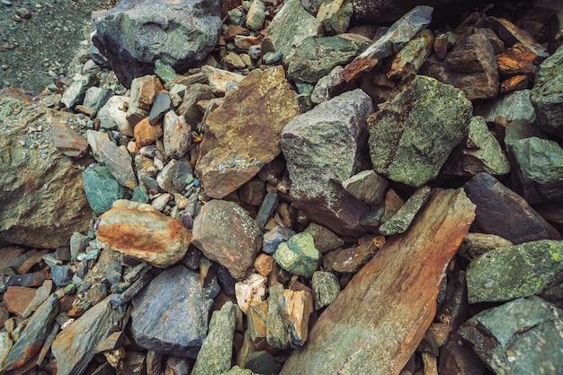 Fluxo de pedregulhos multicoloridos. pedra solta perto acima. pedras espalhadas aleatoriamente na natureza. fundo detalhado surpreendente de pedregulhos das montanhas com musgos e líquenes. textura natural do terreno da montanha.