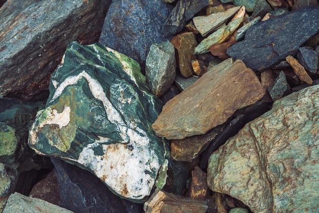 Fluxo de pedregulhos multicoloridos. pedra solta perto acima. pedras espalhadas aleatoriamente na natureza. incríveis pedregulhos das montanhas com musgos e líquenes. textura natural do terreno da montanha.