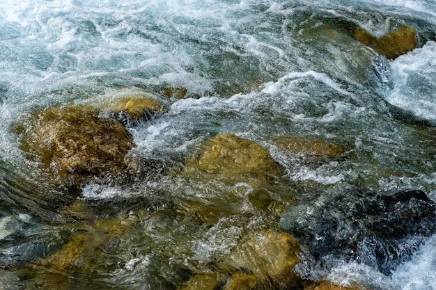 Fluxo poderoso de água sobre as pedras, ascendente próximo do rio da montanha.