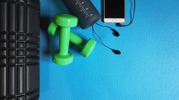 Foam roller com halteres verdes e garrafa de água e telefone com fones de ouvido - ginásio fitness equipment fundo azul auto liberação miofascial - mfr.