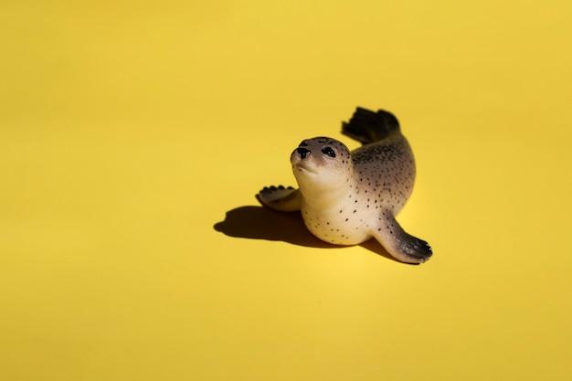 Foca de brinquedo bonito em um fundo amarelo brilhante com espaço de cópia. design para tecido, têxtil, decoração.