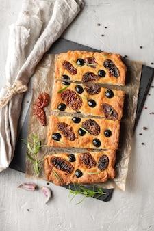 Focaccia assada com tomate, azeitonas pretas e alecrim. pão caseiro italiano natural. vista do topo.