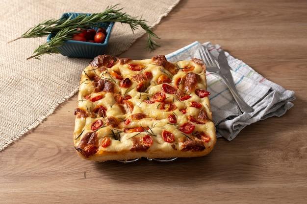 Focaccia caseira com alecrim, azeite e tomate na mesa de madeira.