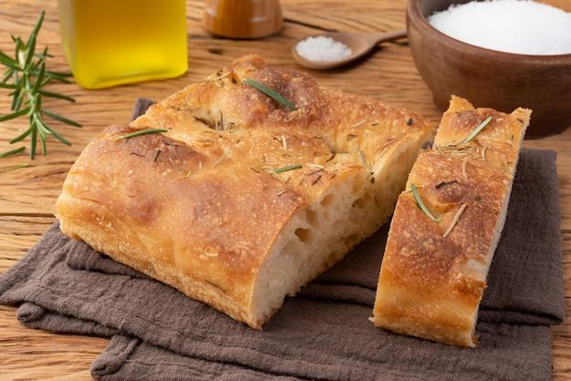 Focaccia caseira com sal, azeite e alecrim sobre mesa de madeira.