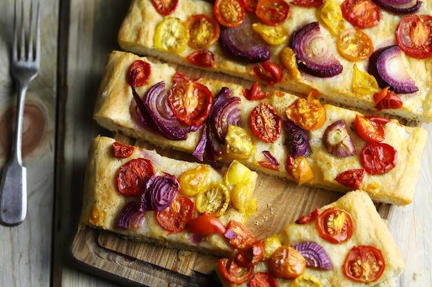 Focaccia caseira fresca com cebola azul e tomate cereja.