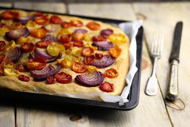 Focaccia caseira fresca com tomate e cebola azul.