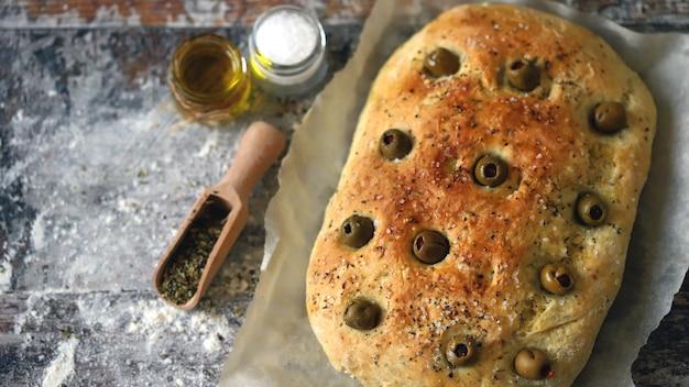 Focaccia caseiro fresco com ervas italianas. cozinhando em casa. pão italiano tradicional com azeitonas.